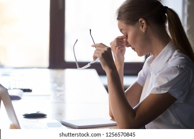 Young tired woman worker student taking off holding glasses massaging nose bridge taking break to rest feeling eye strain after computer work, bad blurry weak vision eyestrain tension fatigue concept
