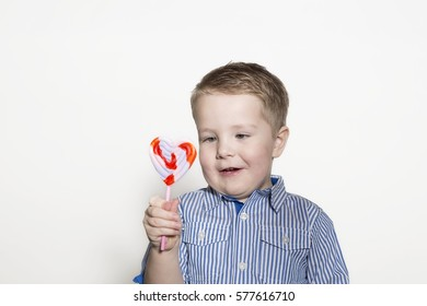 Young toddler about to eat a heart shaped sucker