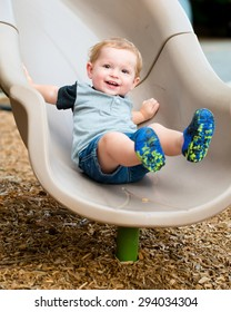Young toddler boy child playing on slide at playground outdoors during summer