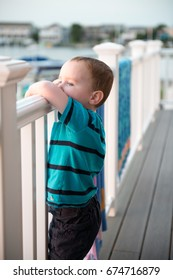 Young toddler boy on patio deck outside at sunset down at shore