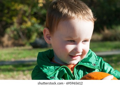 Young toddler boy outside holding a pumpkin with pumpkin fields in the background