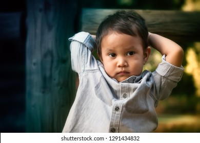 Young toddler boy that looks troubled, worried, or expressing anti social behavior while holding his head with his arms.
