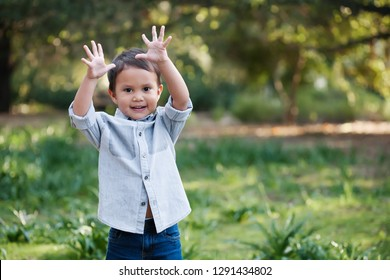 Young toddler boy using his hands to express himself, standing outdoors in a green field looking happy.