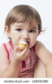 young toddler eating pastry with pleasure