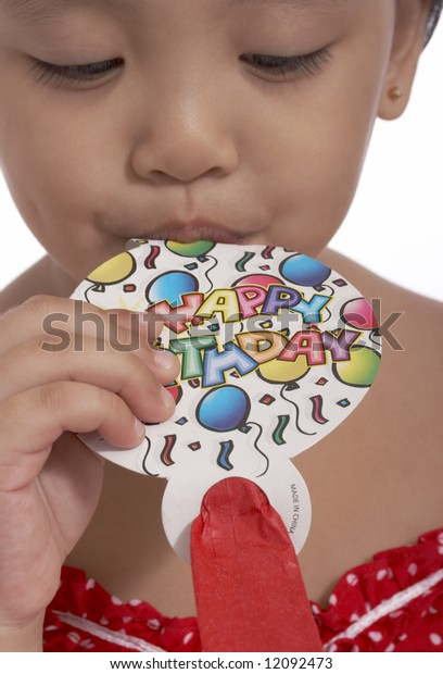 young toddler girl blowing a party popper