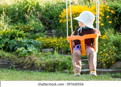 young toddler girl in hat sitting in the safe swing in the summer garden with blooming flowers