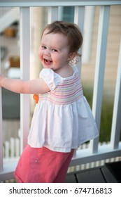 Young toddler girl on patio deck outside at sunset down at shore