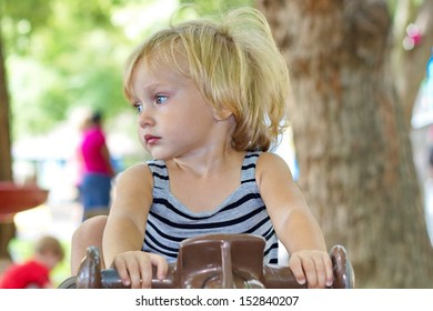 A young toddler girl riding a toy at the park as she looks away wistfully at something else she'd like to do.