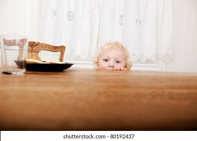 A young toddler peeking over the edge of the table before meal time