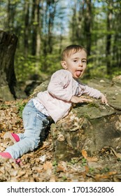 young toddler playing in the forest, tongue sticking out
