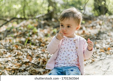 young toddler playing in the forest, touching her nose