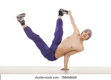 Young topless male dancer sitting on one hand, performing streetdance position , wearing ultraviolet pants. Horizontal image with copyspace, in studio, on white background and wood floor.