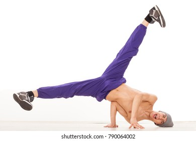 Young topless male dancer sitting on one hand, performing streetdance position , wearing ultraviolet pants, with legs apart and head on the floor. Studio, on white background and wood floor.