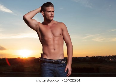 young topless man outdoor holding back his hair while looking away from the camera with the sunset behind