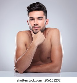 young topless man is thinking while seated at a desk in studio