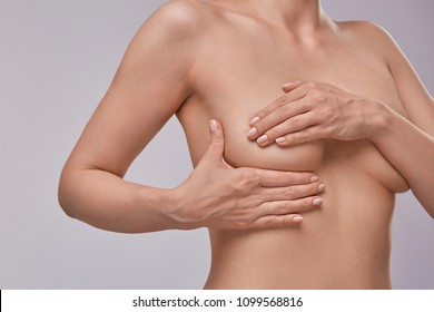 Young topless woman doing breast self-exam (BSE). Checking up breast changes, possible lumps, distortions or swelling.  Breast cancer awareness.