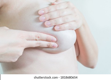 Young topless woman doing breast self-exam (BSE). Checking up breast changes, possible lumps, distortions or swelling.