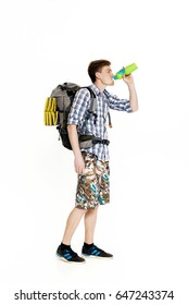 Young tourist with  backpack drinking water on white background
