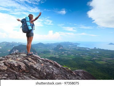 Young tourist with backpack enjoying valley view from top of a mountain