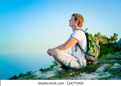 young tourist with backpack sitting on the hill and enjoy the scenery