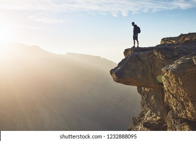 Young tourist with backpack standing on the edge of cliff at sunrise. Jebel Akhdar, Grand Canyon of Oman.