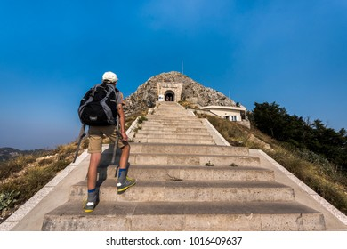 Young tourist boy  with backpack climbing the steep stairs to Njegusi mausoleum in Lovcen National Park, Montenegro