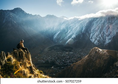 Young tourist in bright hat, black trousers with a backpack sit on cliff's edge and looking at the misty mountain village and glacier at sunrise, Stepantsminda, Georgia. Enjoyment concept