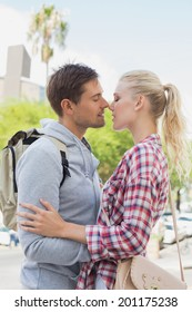 Young tourist couple about to kiss on a sunny day in the city