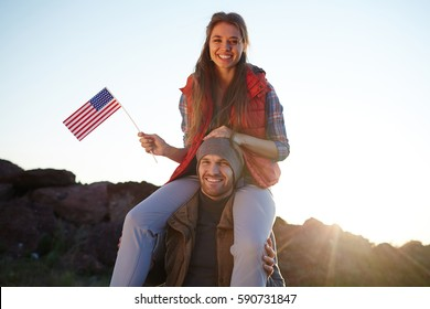 Young tourist couple celebrating American freedom: beautiful girl in hiking outwear sitting on her boyfriends shoulders smiling cheerfully to camera and waving small American flag at sunset