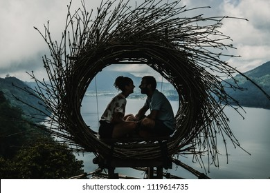 Young tourist couple enjoying their tour of the island of Bali, Indonesia. Making a stop on a beautiful hill overlooking a large lake. Photographs in a straw nest, natural environment. Loving couple.
