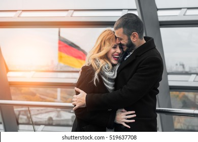 Young tourist couple and German flag in beautiful Reichstag building interior, German Bundestag, in Berlin, Germany