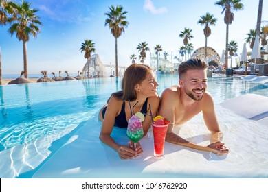 Junges Touristenpaar im Überendpool mit Cocktails im Resort am Strand