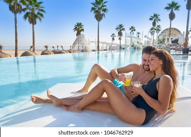 Joven pareja de turistas en la piscina infinita hamaca en el complejo en la playa tomando refrescos