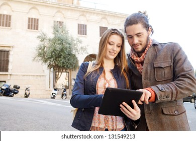 Young tourist couple standing together in a destination city holding and sharing a digital tablet pad while on vacation, smiling.