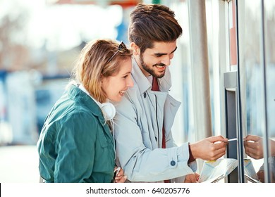 Young tourist couple using ATM early in the morning.