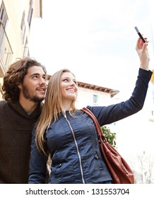 Young tourist couple visiting a destination city and taking pictures of the classic buildings while on vacation in Europe.