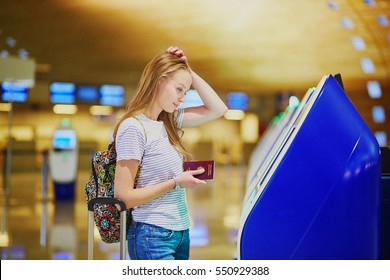 Young tourist girl with backpack and carry on luggage in international airport, doing self check-in, looking upset and worried. Delayed or missed flight concept