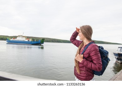 Young tourist girl with a backpack waiting for the ferry