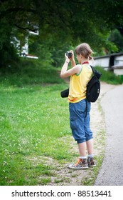 young tourist girl with camera taking landscape picture
