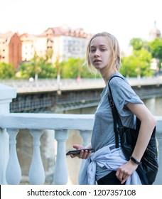 Young tourist girl on a bridge in a European city.