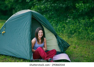 a young tourist girl is sitting in a tent in the forest
