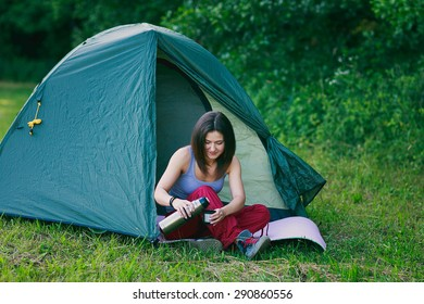 a young tourist girl is sitting in a tent in the forest and pouring coffee from thermos