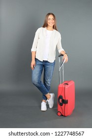 Young tourist girl in summer casual clothes, with red suitcase, passport, tickets isolated on grey background.