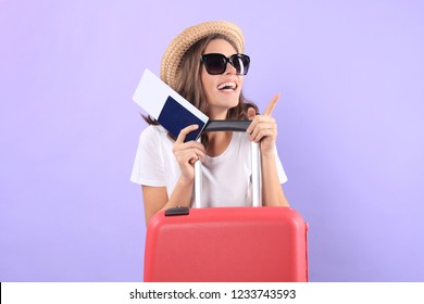 Young tourist girl in summer casual clothes, with sunglasses, red suitcase, passport isolated on purple background