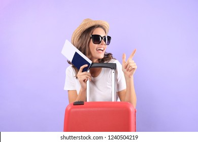 Young tourist girl in summer casual clothes, with sunglasses, red suitcase, passport isolated on purple background.