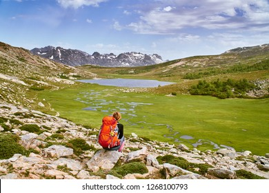 Young tourist girl watching Lac de Nino lake in Corsica mountains with blue sky and clouds GR20