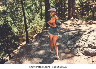 Young tourist girl wearing cap and sunglasses and carrying her backpack, descending into a valley and looking back over her shoulder.