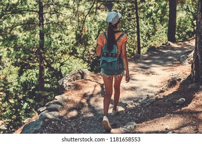 Young tourist girl wearing cap and carrying her backpack, descending into a valley and enjoying the view of high mountains with green trees.