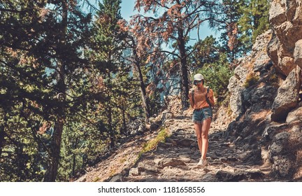 Young tourist girl wearing cap and sunglasses and carrying her backpack, descending into a valley and enjoying the view of high mountains with green trees.