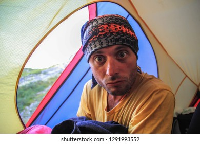 A young tourist guy sits inside a yellow tent at the campsite and makes faces